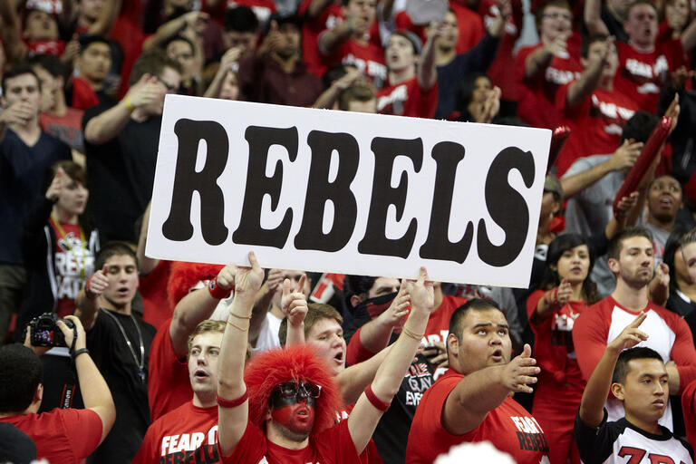 Crowd of students holding up a Rebels sign.