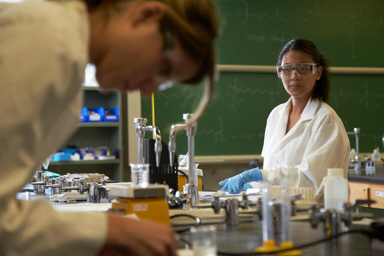Two students in lab coats and goggles attend an organic chemistry lab class