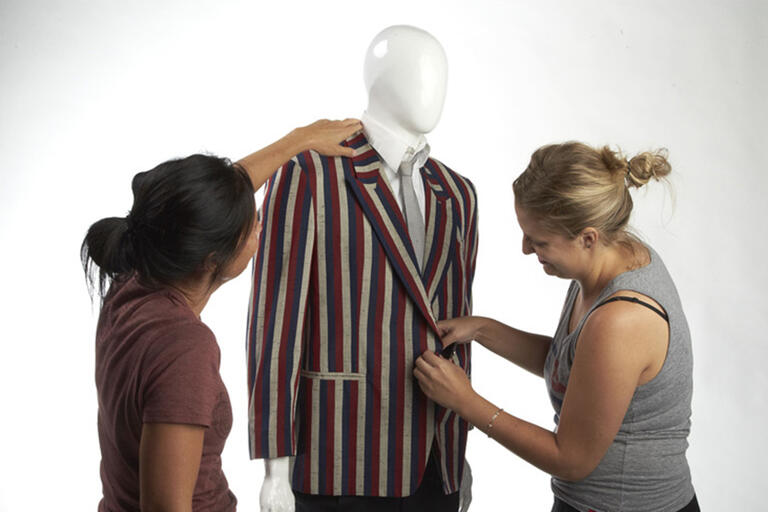 Two women measuring a coat on a mannequin.