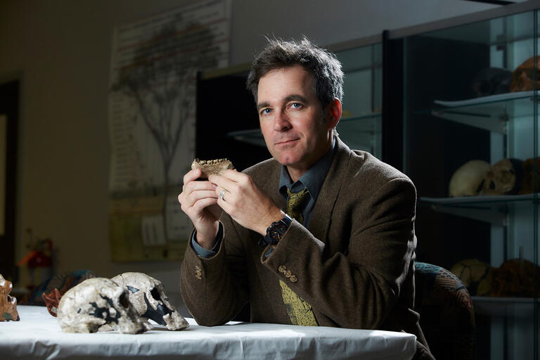 Brian Villmoare sits at a desk and holds a fossil