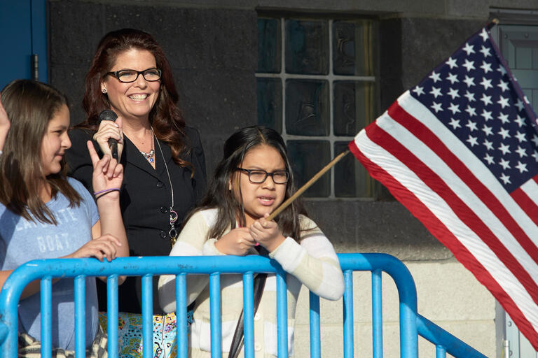 Principal Kathleen Decker leads the school's morning routine next to an American flag.
