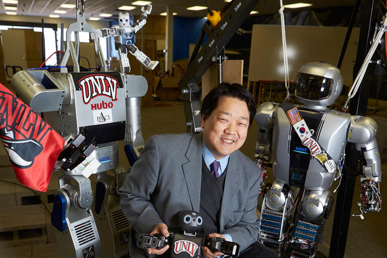 Paul Oh poses with a few of his robots