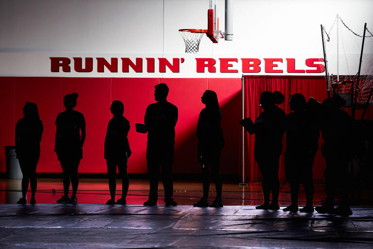 Silhouettes of students inside of basketball gym.