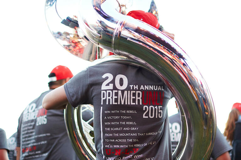 student with back to camera displays Premier 2015 shirt while holding tuba