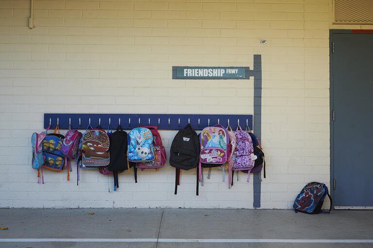 Several childrens backpacks hanging on the wall