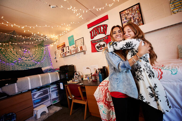 Female students hugging inside of UNLV dorm.