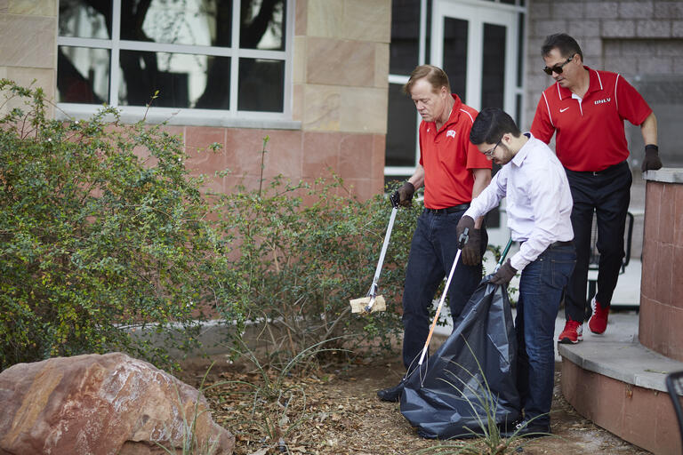 From left, Chief of Staff Fred Tredup, Special Assistant to the Chief of Staff Joseph Dagher and President Len Jessup clean up the bushes outside William S. Boyd Hall. (Josh Hawkins/UNLV Creative Services)