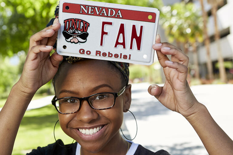 Mecca Walker holds up UNLV license plate
