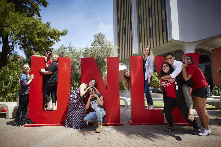 Students climb over metal letters spelling U-N-L-V