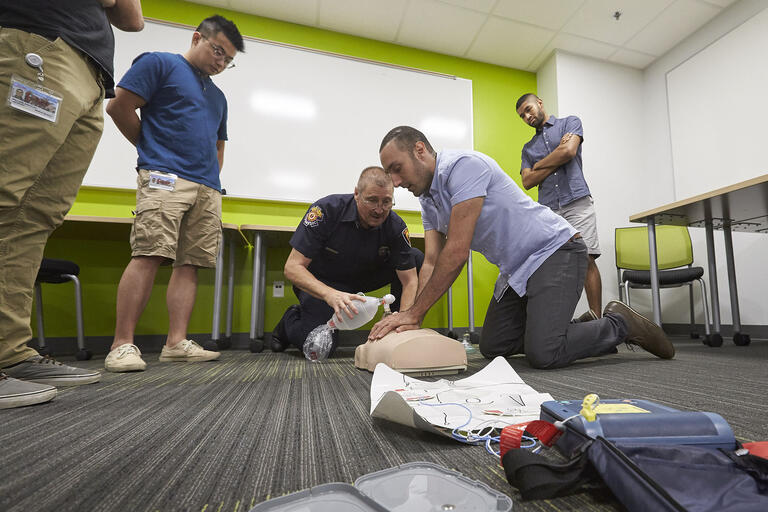 man doing compressions on CPR mannequin