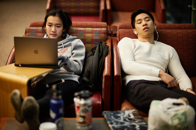 woman with laptop next to sleeping man
