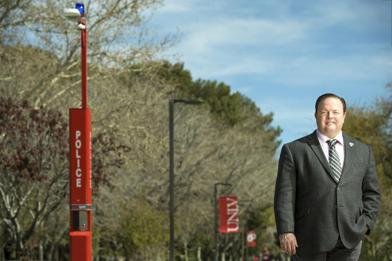 Portrait of Yuri Graves, UNLV's first emergency manager, stands by a call box.