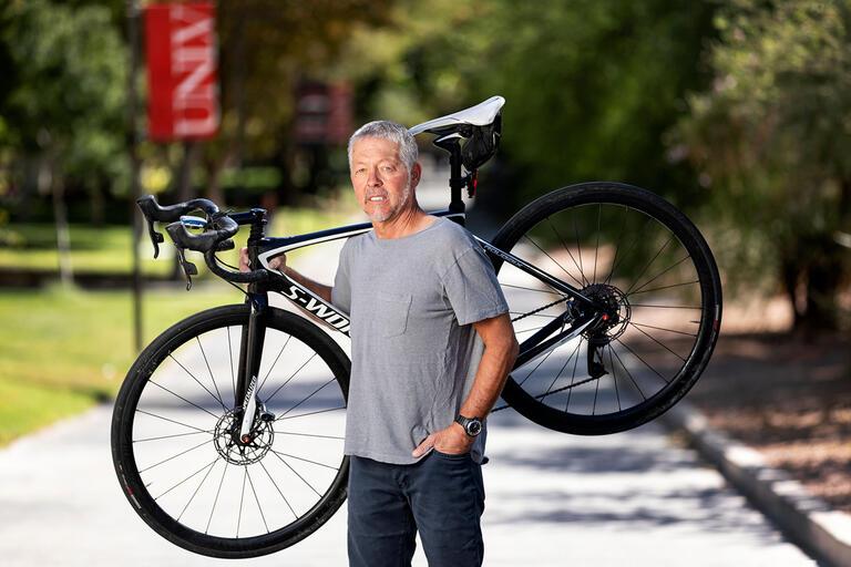 Brett Riddle holding a bike.
