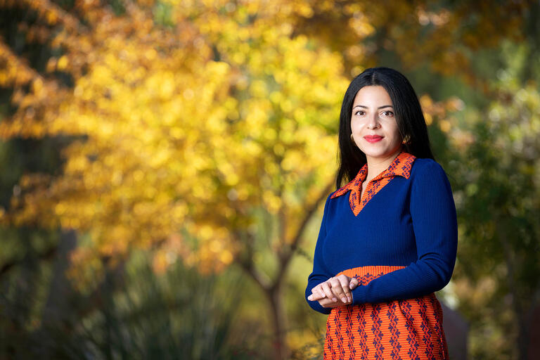 Sara Ortiz, program manager for the Black Mountain Institute. She manages events, readings, etc. for the fellows and writers-in-residence, poses in front of trees on campus.