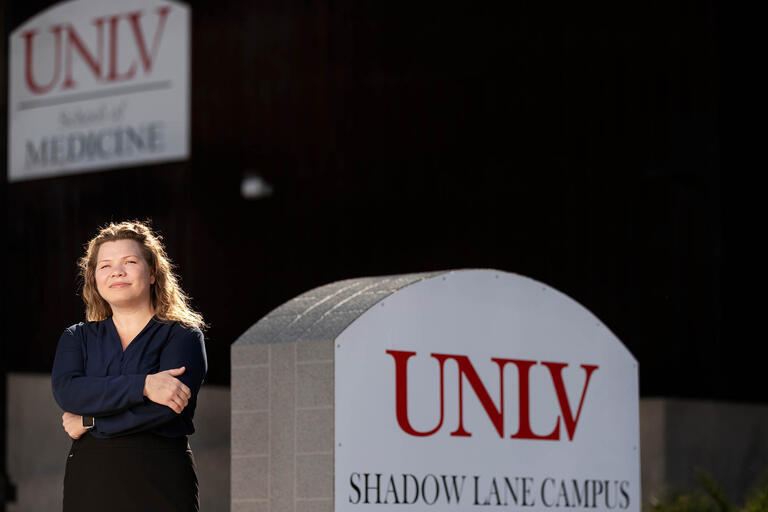 Cyndi Backstrom, a manager of IT Support Services Poses in front of UNLV sign.