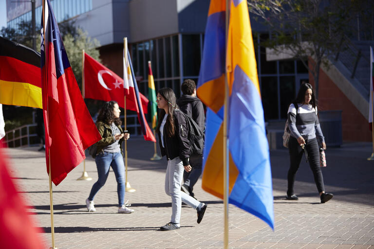A variety of flags from around the world decorate the plaza with students walking between them.
