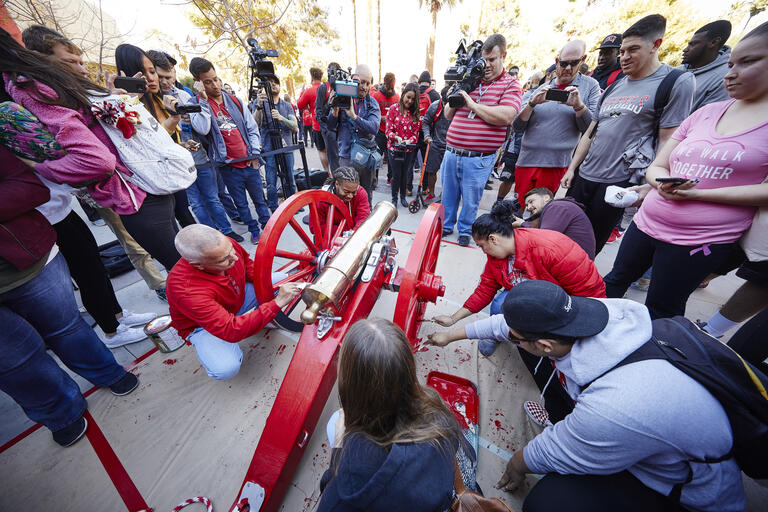 A crowd gathers to paint the Fremont Cannon scarlet.