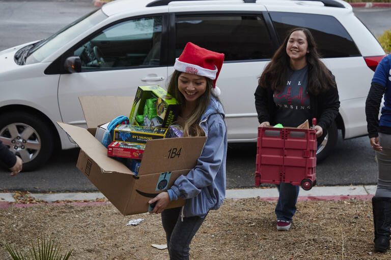 UNLV students carrying boxes of gifts