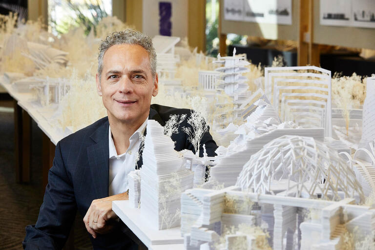 Steffen Lehmann poses in front of architectural models.