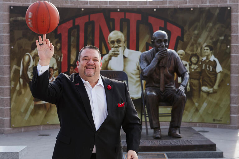 Joe Esposito, special assistant to head basketball coach Marvin Menzies, poses in front of the Tarkanian statue in front of the Thomas & Mack Center.