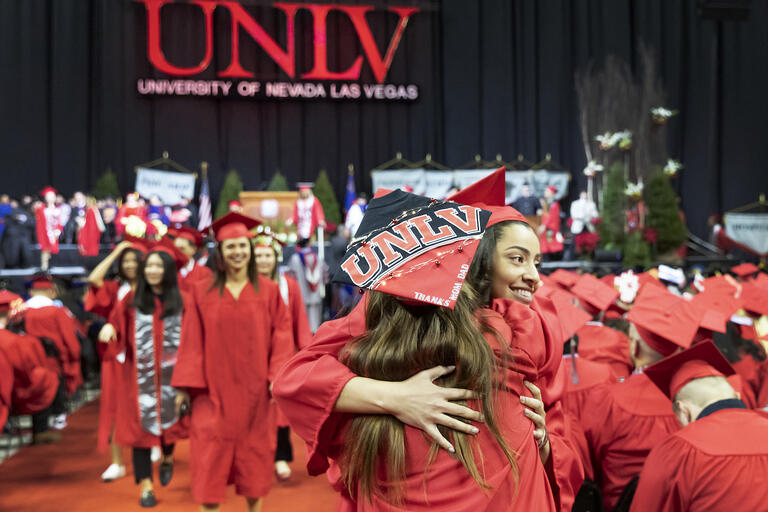 UNLV students in red caps/gowns hugging at commencement