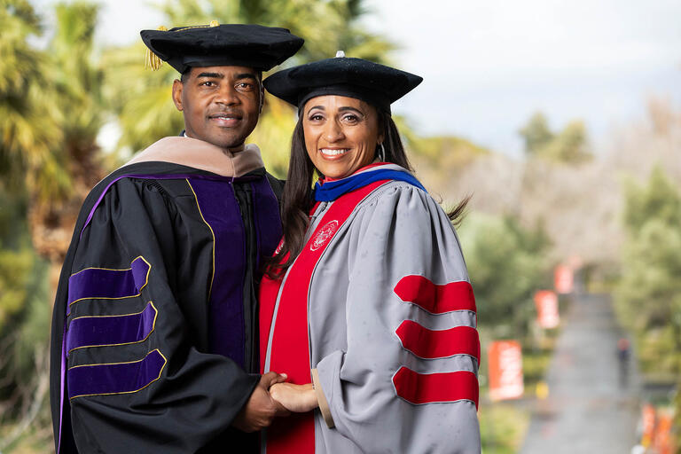 Keith Rogers and Rebecca Rogers, wearing graduation robes, pose overlooking a pathway on the UNLV campus.