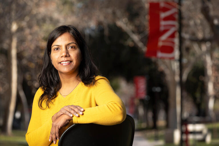 Soumya Upadhyay, poses in front of UNLV banners on campus.