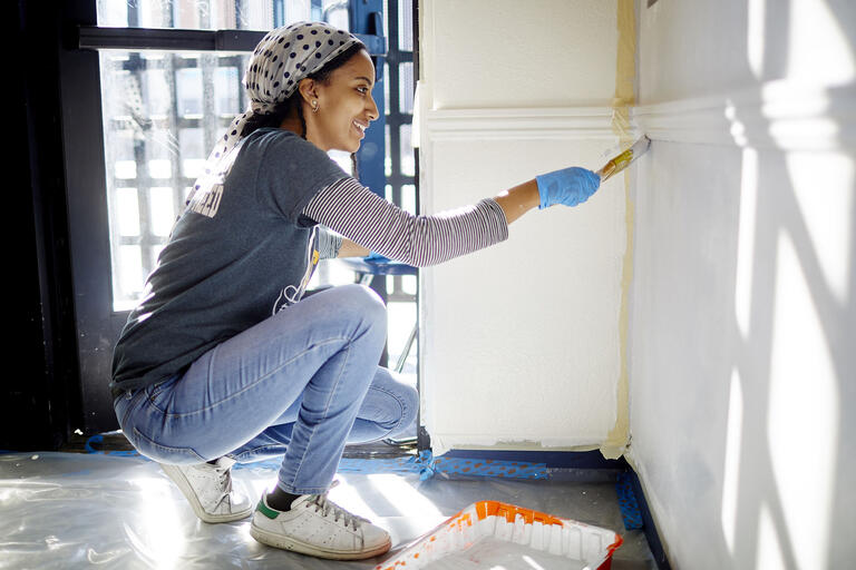 A student kneels with a paint brush to put a fresh coat of white paint on a wall.
