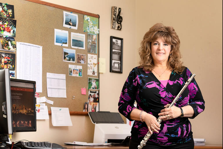 Cameryne Kelley holds a flute while posing in front of a bulletin board in her office.