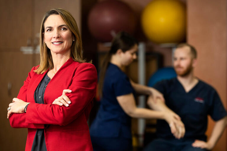 Professor Jennifer Nash poses in front of physical therapy students performing an exam.