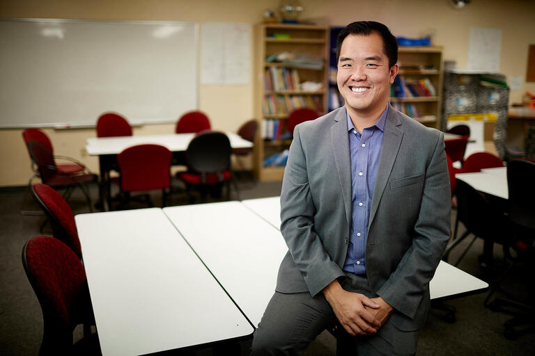 Frederick Ngo poses in front of tables and chairs in a classroom.