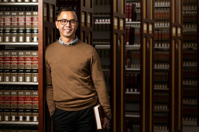 Pete Reyes poses next to a bookshelf.