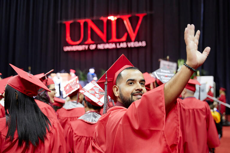 UNLV student in cap and gown waves to crowd during commencement