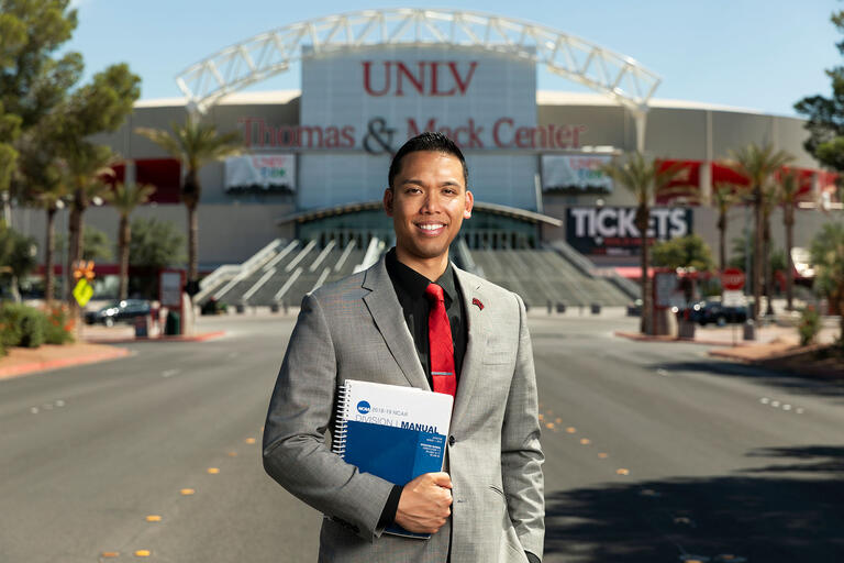 Eric Nepomuceno standing, with book in hand, in front of the Thomas & Mack