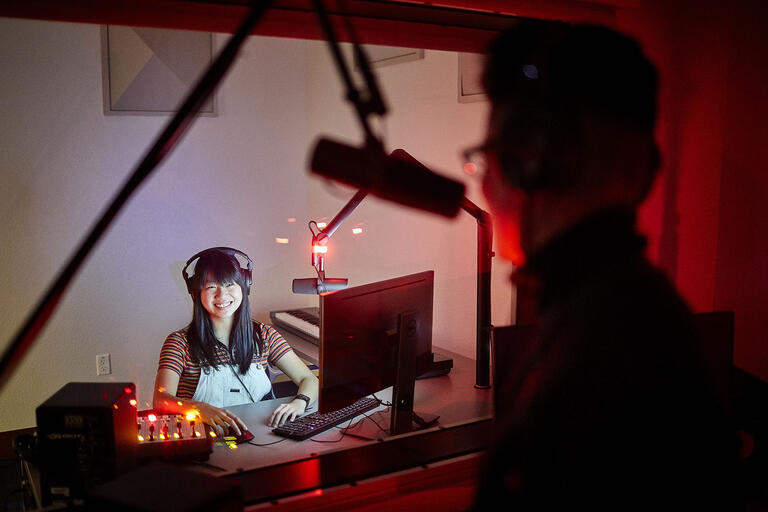 woman in audio recording studio looking through window at performer