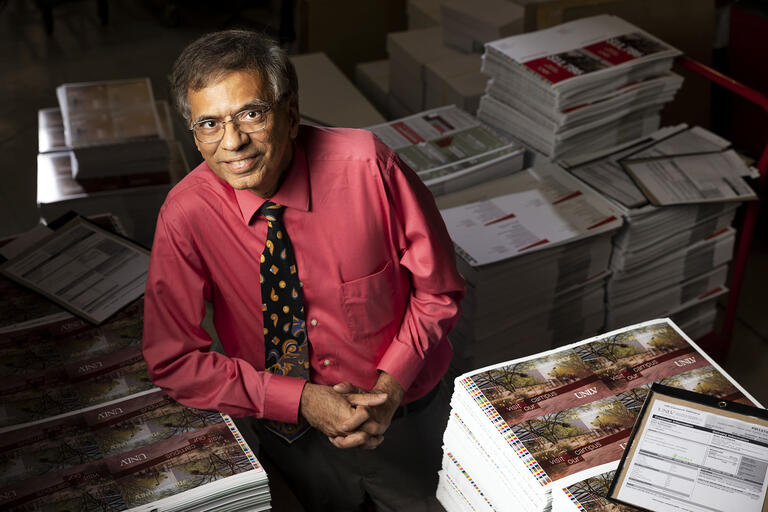 Abbas Badani poses in front of UNLV's printouts.