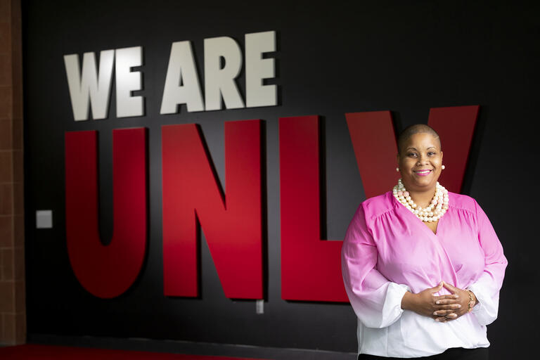 "Renee Watson stands in front of ""We Are UNLV"" sign."