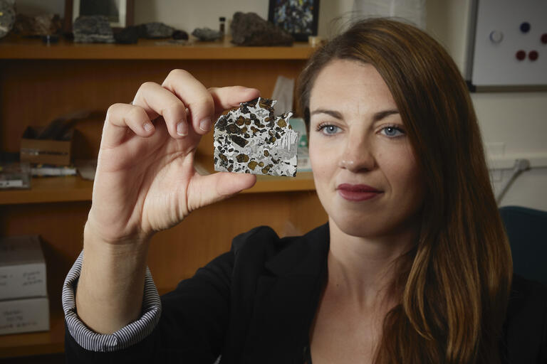 unlv professor arya udry looks at a meteorite that she's holding up to the light