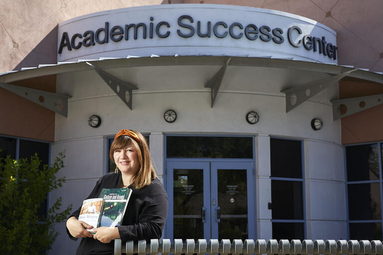 Hanna Andrews holding books in front of the Academic Success Center