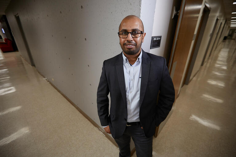 Harsha Perera, Ph.D. Assistant Professor Educational Psychology and Higher Education poses in a hallway.