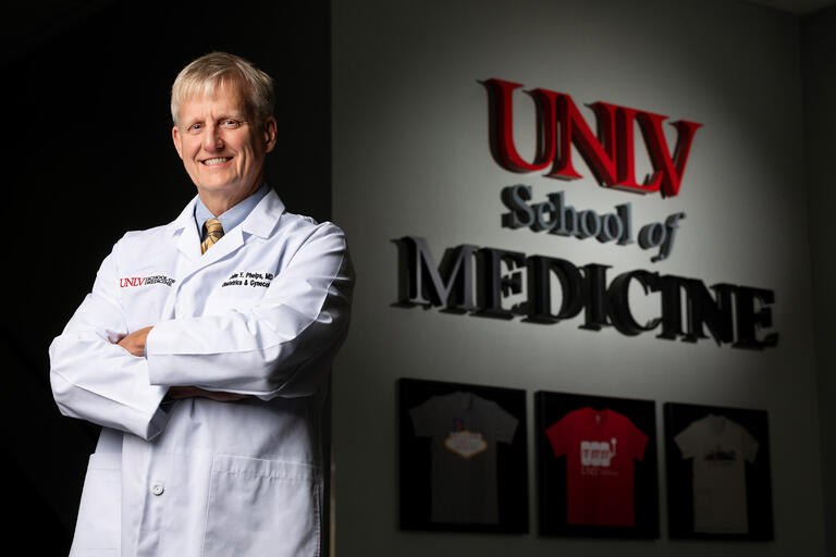 Dr. John Phelps, poses in front of the UNLV School of Medicine sign.