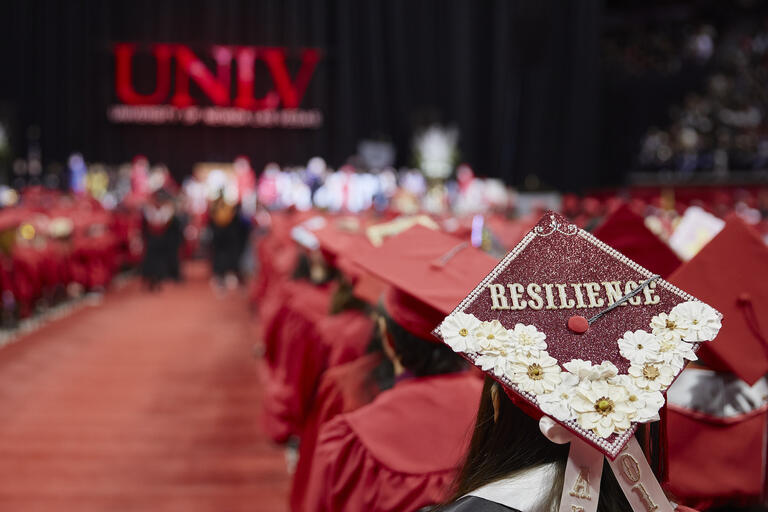 Graduates seated in red caps and gown during a previous UNLV commencement