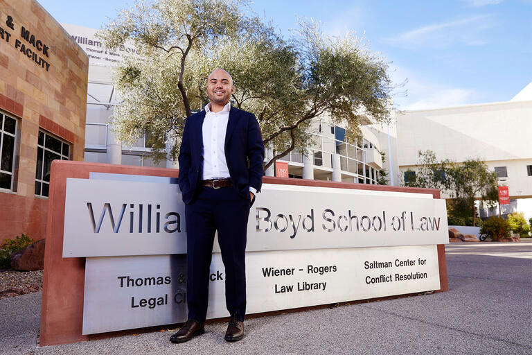Cameron Lue-Sang standing in front of William Boyd School of Law sign.