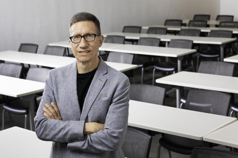 man standing in empty classroom with rows of desks behind