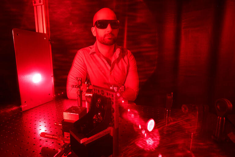 Portrait of Physics and astronomy professor Ashkan Salamat in red light.