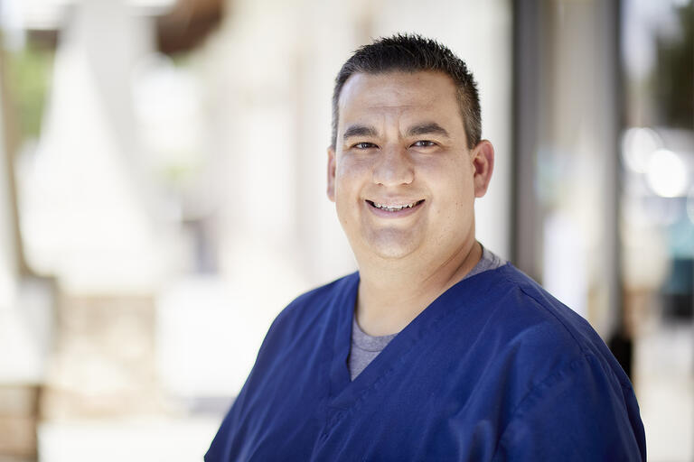 Portrait of Dr. Daniel Diaz wearing blue scrubs. Diaz is playing a key role in day-to-day operations at UNLV Medicine's COVID-19 curbside test operation
