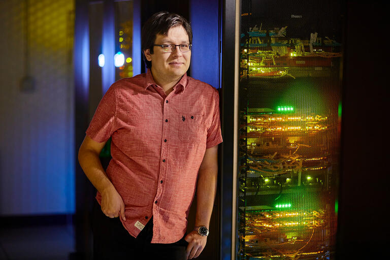 Computer Science Faculty-In-Residence Jorge Fonseca by server racks.