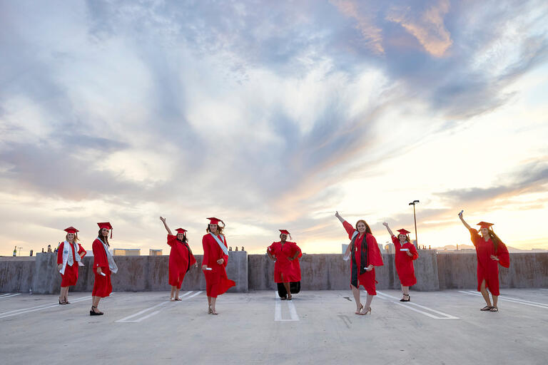 Eight UNLV graduates pose for a photo in their graduation attire.