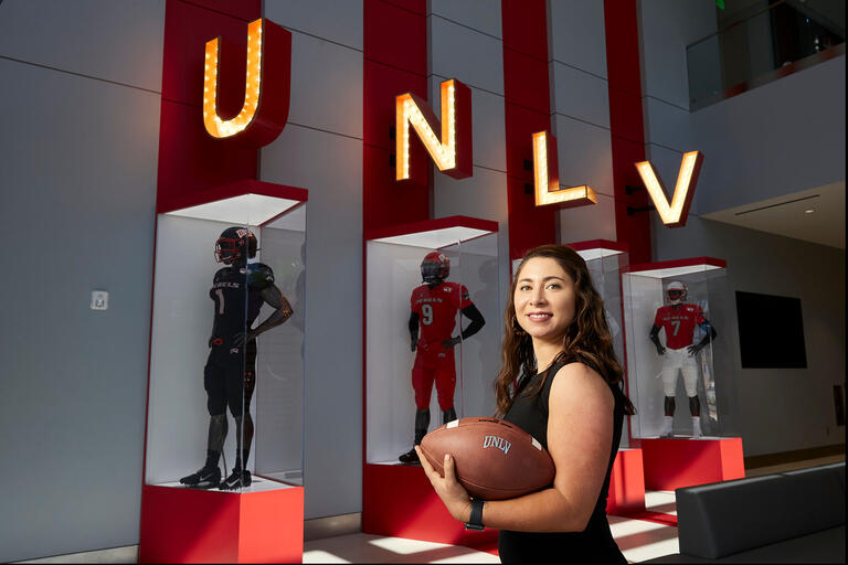Brittany Boehm holding football in Fertita Football Complex lobby.