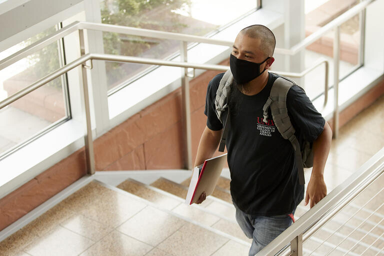 student wearing mask walking up stairs